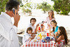 M021, TA1.18: New spot photo of a young mom or dad on the beach or in a park (or in a similar recreational setting) with the kids playing nearby; the parent should be talking on a cell phone, stressed out, serious.<br /> Choice 1 of 8